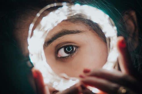 videntes mujer joven mirando por un círculo de luz